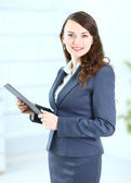 Portrait of a cute young business woman with the work plan smiling, in an o — Stock Photo