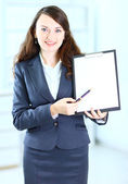 Portrait of a cute young business woman with the work plan smiling. — Стоковое фото