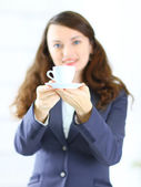 Business woman offers a cup of coffee in the office — Stok fotoğraf