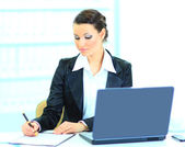 Beautiful businesswoman fills the plan of work in the office. — Stock Photo