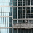Window washer cleaning windows on a modern highrise office - Stock Photo