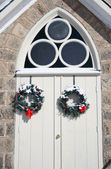 Arched curch entrance doors with christmas wreaths in winter — Stock Photo