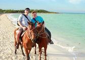 Romantic horseback riding on ocean beach — Stock Photo
