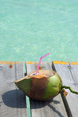 Coconut drink overlooking tropical beach — Stock Photo