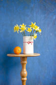Bouquet narcissus in vase and orange fruit — Stock Photo