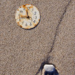 Stock Photo: Rusted clock dial on sebeach sand