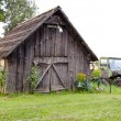 Old farm wooden building and broken tractor — Stock Photo #9012062