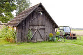 Old farm wooden building and broken tractor — Stock Photo