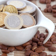 Coffee cup full of Euro coins, spilled coffee beans — Stock Photo
