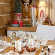 Christmas table set with candles, sculptures and christmas tree — Stock Photo #8100512