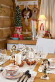 Christmas table set with candles, sculptures and christmas tree — Stock Photo
