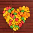 Colorful dragees of peanuts arranged in a shape of heart - Stock Photo
