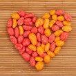 Colorful dragees of peanuts in a shape of heart — Stock Photo