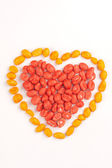 Red heart and yellow contour made of dragees of peanuts — Stock Photo
