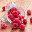 Stock Photo: Fresh raspberries spilling from cup