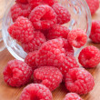 Fresh raspberries spilling from a cup - Stock Photo