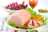 Luncheon meat, salad, olives and grapes — Stock Photo