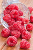 Fresh raspberries spilling from a cup — Стоковое фото