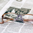 Reading glasses lying on a newspaper — Stock Photo