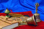 Two Tibetan ritual bell and a book — Stock Photo