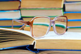 Reading glasses lying on the book — Stok fotoğraf