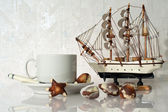 Still life with cup, candy and yacht — Stock Photo