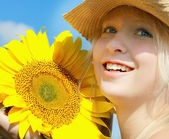 Young smiling girl holding ripe sunflower in her hands — Stock Photo