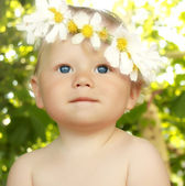 Smiling baby in a flower wreath — Stock Photo