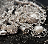 Various silver shining jewellery and closeup pearl on black — Stock Photo