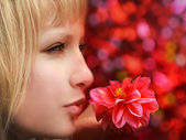 Closeup profile of beautiful blond woman with flower on red background — Stock Photo