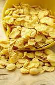 Inverted bowl of yellow corn flakes on the table — Stock Photo