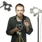 Photographer with retro camera in studio — Stock Photo