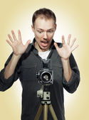 Shocked photographer with retro camera — Zdjęcie stockowe