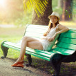 Girl sitting on a bench — Stock Photo #9486041