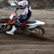 Stock Photo: Departure with acceleration out of left-turn motocross