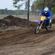Motorcyclist rides motocross track on knolls - Stock Photo