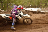 Rider stuck in deep ruts turning the sandy motocross track — Stock Photo