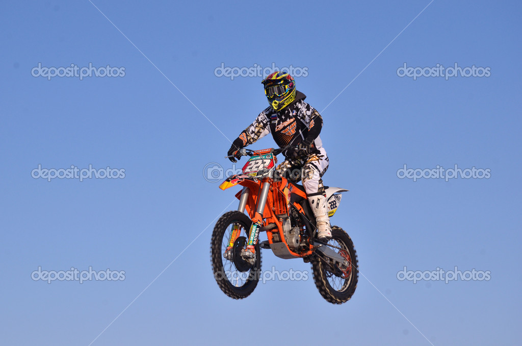 RUSSIA, SAMARA - JANUARY 3: Rider motorcycle D. Vintaev performs a jump in background of blue sky, practice motocross on January 3, 2012 in Samara, Russia  Stock Photo #8389878