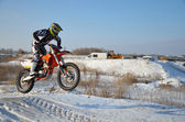 Motorcycling rider on the bike jumps from a hill on a snowy high — Stock Photo