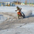 MX rider on motorcycle moves in a turnabout with skid in snow - Stock Photo