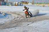 MX rider on motorcycle moves in a turnabout with skid in snow — Stock Photo
