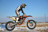 Rider on bike for motocross flies over hill on snowy highway — Stock Photo