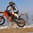 Motocross, motorcycle driver flies over hill out of snow — Stock Photo