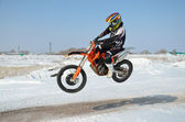 Motocross driver flies over hill out of snow — Stock Photo