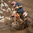 Motocross racer is turning in gauge line with a spray of dirt - Stock Photo