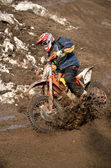 Motocross racer is turning in gauge line with a spray of dirt — Stock Photo
