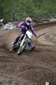 Departure with acceleration out of the left-turn motocross racer — Stock Photo