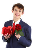 A guy with a red rose and a present — Stock Photo