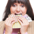 Studio shot of woman eating pills - Stock Photo