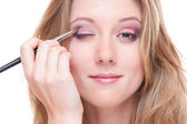 Studio shot of beautiful young woman doing make up — Stock Photo